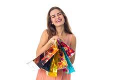 Houdt het pret mooie meisje die haar ogen sluiten pakketten van opslag die op witte achtergrond worden geïsoleerd Royalty-vrije Stock Foto
