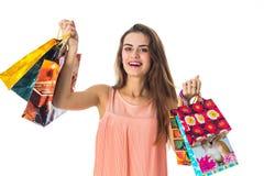 Houdt het pret mooie meisje vele verschillende pakketten met giften en lacht close-up Stock Afbeelding