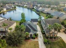 Houes et porches d'écran rayent la banque d'un petit étang dans un voisinage américain d'antenne ci-dessus image stock