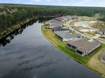 Houes and Screen Porches Line the Bank of a Small Pond in an American Neighborhood from Above Aerial stock image