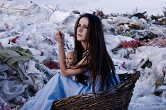 Houghtful女孩在一个老篮子的垃圾填埋在手上坐与一个老玩偶 免版税库存照片