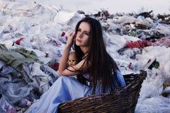 Houghtful女孩在一个老篮子的垃圾填埋在手上坐与一个老玩偶 免版税库存图片