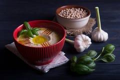 Houmous fait maison avec le basilic, l'ail et l'huile d'olive Photographie stock