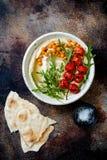 Houmous fait maison avec les tomates-cerises r?ties Cuisine arabe traditionnelle et authentique du Moyen-Orient photographie stock