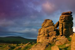 Hound Tor. Magenta clouds drift over Hound Tor on Dartmoor in Devon UK as the rocks are bathed in the golden glow of the rising sun Royalty Free Stock Photos