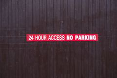 24 hour access no parking sign red and white on wooden access door royalty free stock photos