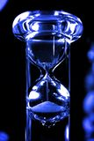 Hour Glass. Sand slipping through an hour glass highlighted in blue Royalty Free Stock Photo