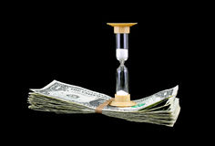 Hour glass atop a stack of cash. An hour glass with the sand dropping on top of money on a black background royalty free stock photos