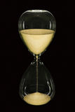 Hour Glass on black. An hourglass showing the sands of time passing isolated on a black background Stock Image