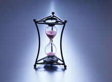 Hour glass. On the blue background royalty free stock photo