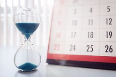 Hour glass and calendar important appointment date, schedule and deadline. Hour glass and calendar concept for time slipping away for important appointment date stock image