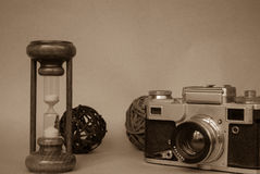 Hour glass with retro photo camera. royalty free stock photography