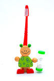 Hour glass with tooth brush. A colorful funny wooden hour glass with red tooth brush looking like a frog for kids to measure time while brushing teeth. Image stock photo