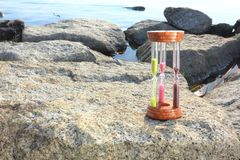 Hour glass triple sand timer on rock formation Royalty Free Stock Images