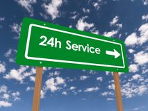 24 Hour Service. 24h Service text graphics on green highway direction sign against blue skies with clouds Royalty Free Stock Image