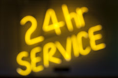 24 Hour Service Neon Sign Message. Message in yellow neon on black background for 24 hour service Stock Photography