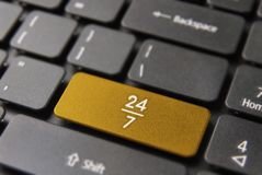 24/7 hour service online in computer key button. 24/7 service online concept, gold computer button with 24 hour icon for always open business Royalty Free Stock Photo
