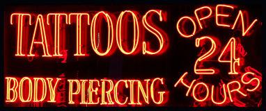 A 24 Hour Tattoo Parlor Neon Sign. A Neon Sign Advertising a Tattoo and Body Piercing Parlor Open 24 Hours royalty free stock images
