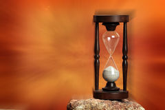 Hourglass. Close up over dramatic red background Stock Photo