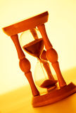 Hourglass. Wooden hourglass on yellow background Royalty Free Stock Photo