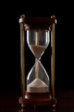 Hourglass. On a dark setting, concept of time passing Royalty Free Stock Photography