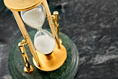 Hourglass. Gold hourglass on marble background Royalty Free Stock Photo