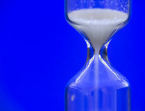 Hourglass. Against a blue background Royalty Free Stock Photo