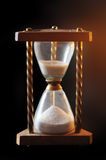 Hourglass. Illuminated by a mysterious light on black background Royalty Free Stock Photo