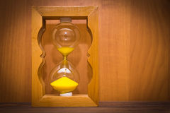 Hourglass as time passing concept for business deadline, urgency and running out of time. Hourglass on wooden background. Concept of passing time for business Royalty Free Stock Photos