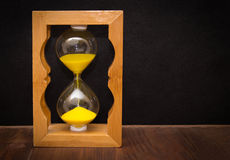 Hourglass as time passing concept for business deadline, urgency and running out of time. Hourglass on wooden background. Concept of passing time for business Stock Photography