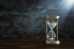 Hourglass as time passing concept in front of black wall background. Conceptual photo on history, fantasy and education.  royalty free stock images