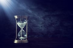 Hourglass as time passing concept in front of black wall background. Conceptual photo on history, fantasy and education.  stock photography