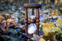 Hourglass on autumn leafs Stock Image