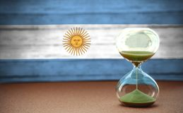 Hourglass on the background of the Argentina flag, the concept of time and countries, space for text royalty free stock photography