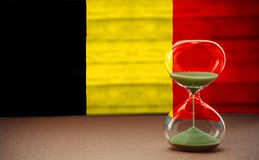 Hourglass on the background of the Belgium flag, the concept of time and countries, space for text royalty free stock images