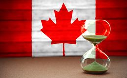 Hourglass on the background of the Canadian flag, the concept of time and countries, space for text stock photos