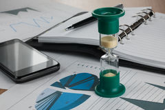 Hourglass on the background of the chart,pen, diary, phone. Stock Images