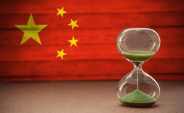 Hourglass on the background of the Chinese flag, the concept of time and countries, space for text royalty free stock photography