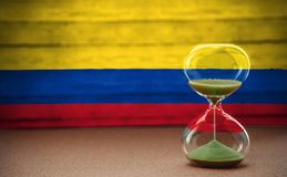 Hourglass on the background of the Colombia flag, the concept of time and countries, space for text royalty free stock photo