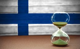 Hourglass on the background of the Finland flag, the concept of time and countries, space for text royalty free stock images