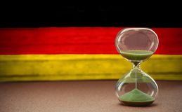 Hourglass on the background of the German flag, the concept of time and countries, space for text royalty free stock photo