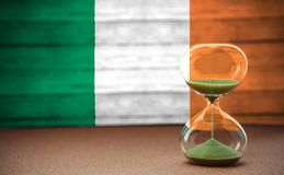 Hourglass on the background of the Ireland flag, the concept of time and countries, space for text royalty free stock images