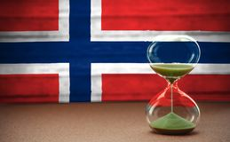 Hourglass on the background of the Norway flag, the concept of time and countries, space for text royalty free stock photos
