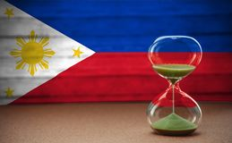 Hourglass on the background of the Philippines flag, the concept of time and countries, space for text royalty free stock photo
