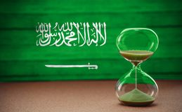 Hourglass on the background of the Saudi Arabia flag, the concept of time and countries, space for text royalty free stock images