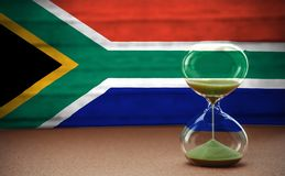 Hourglass on the background of the South Africa flag, the concept of time and countries, space for text royalty free stock photography