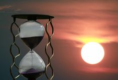 Hourglass on the background of a sunset stock image