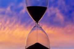 Hourglass on the background of a sunset sky. The value of time in life. An eternity