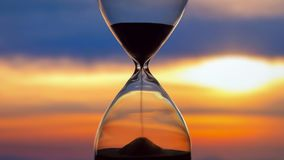 Hourglass on the background of a sunset. The value of time in life. An eternity