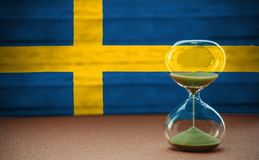 Hourglass on the background of the Sweden flag, the concept of time and countries, space for text royalty free stock photography